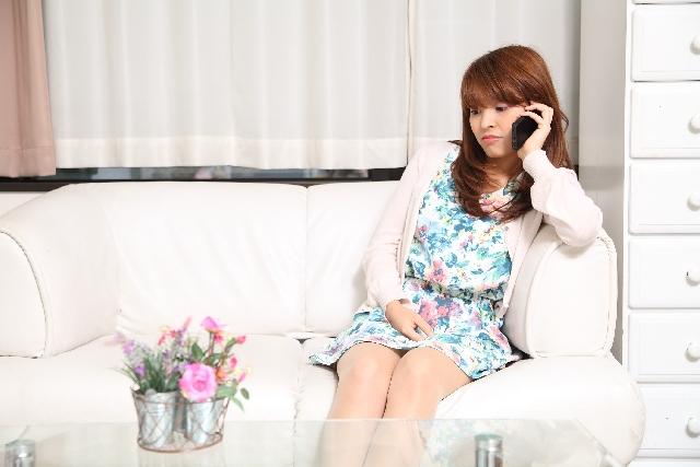 自宅のソファでリラックスしながら電話占いを利用する女性