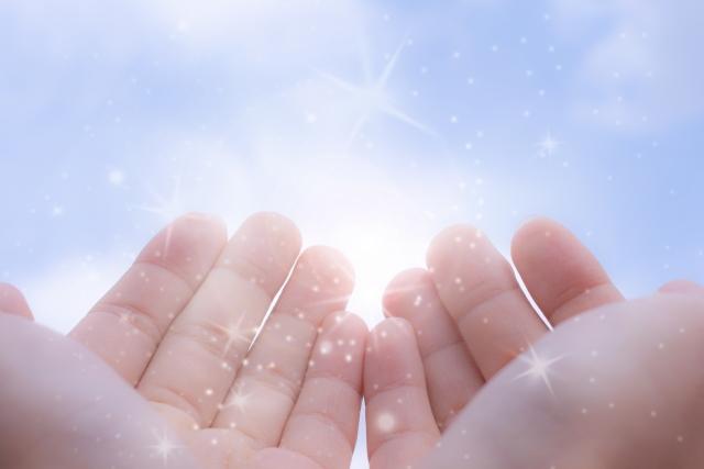 占い師の手から放たれる癒しのエネルギーをイメージ