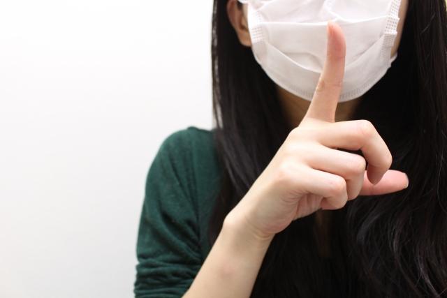 マスクで素性を隠す仕草の女性