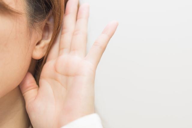 人づてに話を聞くため効く耳を立てる仕草の女性