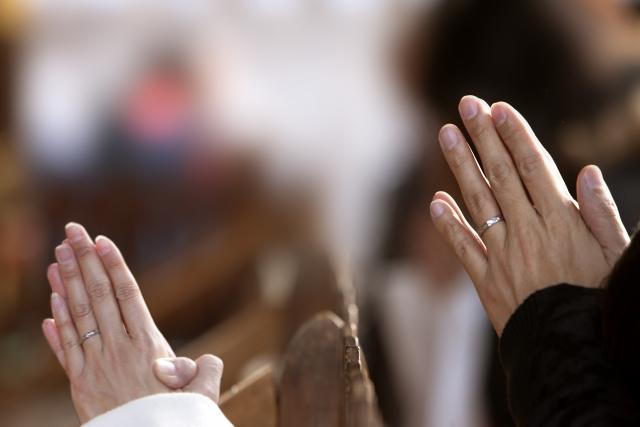 参拝をして手を合わせ幸運を祈る人々