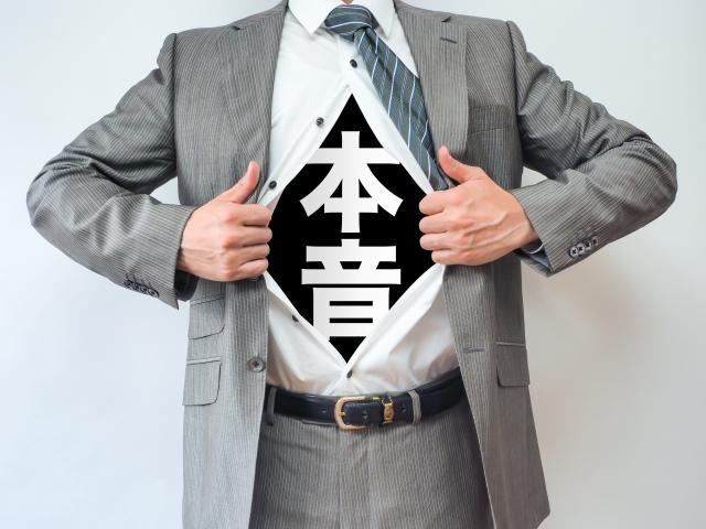 上着を脱ぐとインナーシャツに「本音」と書かれたTシャツを着こんだ男性