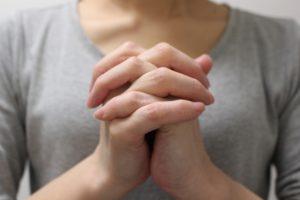 両手を握り祈りを込める女性