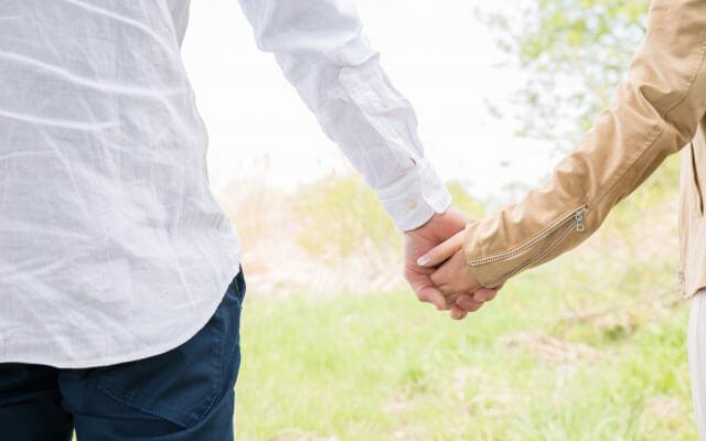 手を繋いで仲睦まじげなカップル