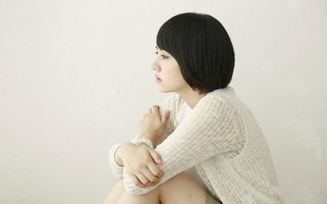 別れた恋人を思い出し独り寂しく膝を抱える女性