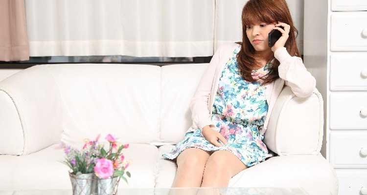 自宅のソファーでリラックスし電話鑑定を受ける女性のイメージ